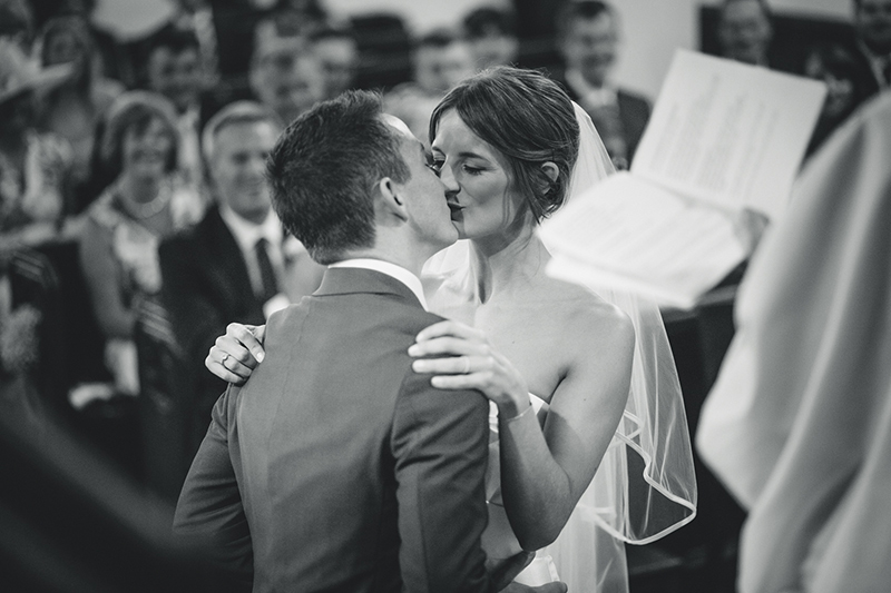 bride and groom kiss each other at their wedding ceremony