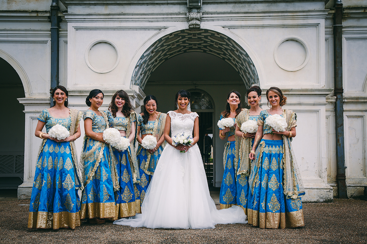 bride and bridesmaids with arch